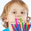 Little cute boy with color pencils on a white background — Stock Photo