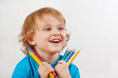 Little blond boy holds color pencils on a white background — Foto Stock