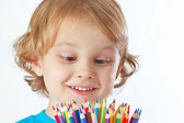 Little cute blond boy looks on color pencils on a white background — Stock Photo