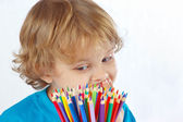 Little cute boy looks on color pencils on a white background — Stock Photo