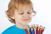 Little blond boy looks on color pencils on a white background — Stock Photo