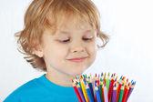 金发碧眼的小男孩看起来上颜色铅笔在白色背景上 — 图库照片