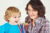 Little smiling boy with his mother with color pencils on a white background — Stock Photo