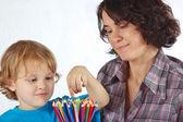 Weinig schattige jongen met zijn moeder met kleur potloden op een witte achtergrond — Stockfoto