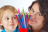 Little boy with his mother with color pencils on a white background — Stock Photo