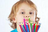 Niño lindo con lápices de color sobre un fondo blanco — Foto de Stock