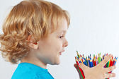 Little child looks on color pencils — Stock Photo