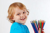 Smiling child with color pencils — Stock Photo