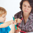 Young mother teaches her son to draw with color pencils — Stok fotoğraf