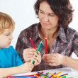 Young mother teaches her child to draw with color pencils — Stock Photo #16771441