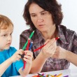 Stock Photo: Young mother teaches her son to draw with pencils