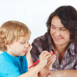 Mother teaches her child to draw with color pencils — Stock Photo