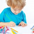 Little blond boy draws with color pencils — Stok fotoğraf