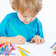 Little blond boy draws with color pencils — 图库照片