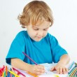 Stock Photo: Little boy draws with color pencils