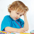 Young cute blond boy draws with color pencils — Stock Photo
