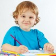 Little smiling boy draws with color pencils on a white background — Stock Photo #16774169