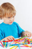 Young blond boy at the table with color pencils — Stock Photo