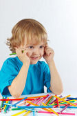 Young cute boy at the table with color pencils — Stock Photo