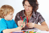 Young mother teaches her child to draw with color pencils — Stock Photo