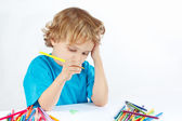 Young blond boy draws with color pencils — Stock Photo