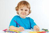 Petit garçon souriant dessine avec des crayons de couleur sur fond blanc — Photo