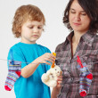 Stock Photo: Mother with her little son hanging toy and clothes