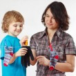 Little boy helps her mother to hang up your glove and socks — Stock Photo