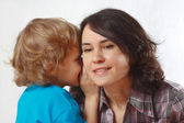 Little blond boy whispers secrets to his mother on a white background — Stock Photo