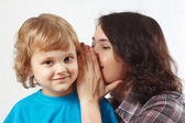 Mother whispers something to her little son — Stock Photo