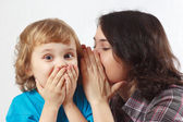 Mother whispers secret to her little son — Stock Photo