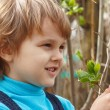 Little blond boy holding bloom leaves outdoors — Stock Photo
