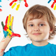 Stock Photo: Young boy with painted hands on background of hand prints