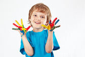 Smiling boy with painted hands on white background — Stock Photo