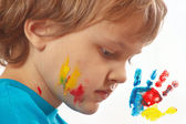 Portrait of a boy with painted face on background of hand prints — Stock Photo