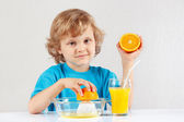 Little blonde boy makes juice from an orange — Stock Photo