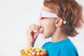 Little boy in 3D glasses eating popcorn — Stock Photo