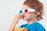Young ironic boy in 3D glasses eating popcorn — Stock Photo