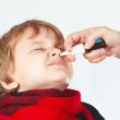 Little boy used a medical nasal spray in the nose — Stock Photo #33009369