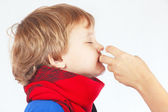 Little sick boy used nasal spray in the nose — Stock Photo
