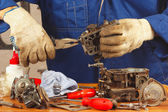 Serviceman repairing old car engine carburetor — Stock Photo