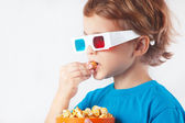 Young ironic boy in stereo glasses eating popcorn — Stock Photo