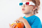 Little blonde boy in 3D glasses with bowl of popcorn — Stock Photo