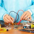 Master checks board of electronic device with a multimeter in service workshop — Stock Photo