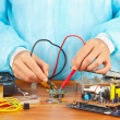 Master checks board of electronic device with multimeter in service workshop — Stock Photo #37295273