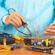 Master solder electronic components of device in service workshop — Stock Photo