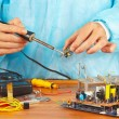 Serviceman solder electronic components of device in service workshop — Stock Photo