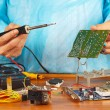 Master solder electronic board of device in service workshop — Stock Photo