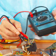 Serviceman checks electronic board with a multimeter — Stock Photo
