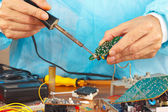 Repair electronic board of device with a soldering iron — Stock Photo